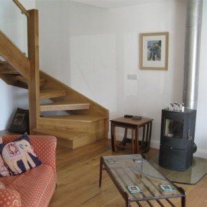 exposed oak staircase and wood burning stove